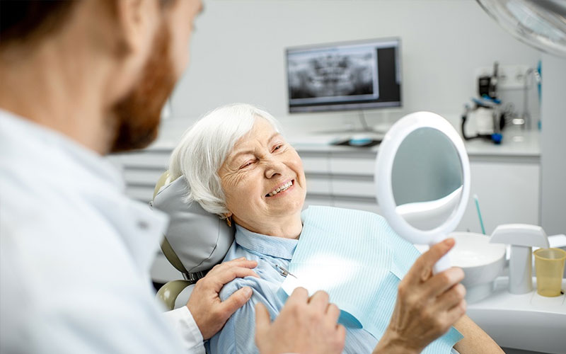 woman-smiling-with-dentures - Aesthetic Dental and Denture Clinic
