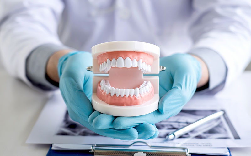 dentures-in-a-hand-of-a-dentist - Aesthetic Dental and Denture Clinic